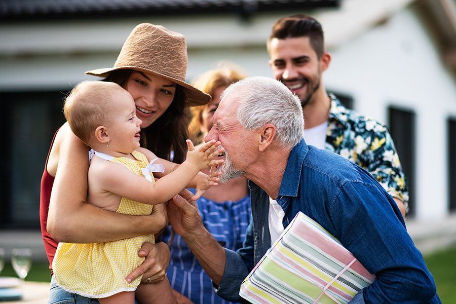 About Our Agency - Happy Baby Touching Grandfathers Face With Family Outside