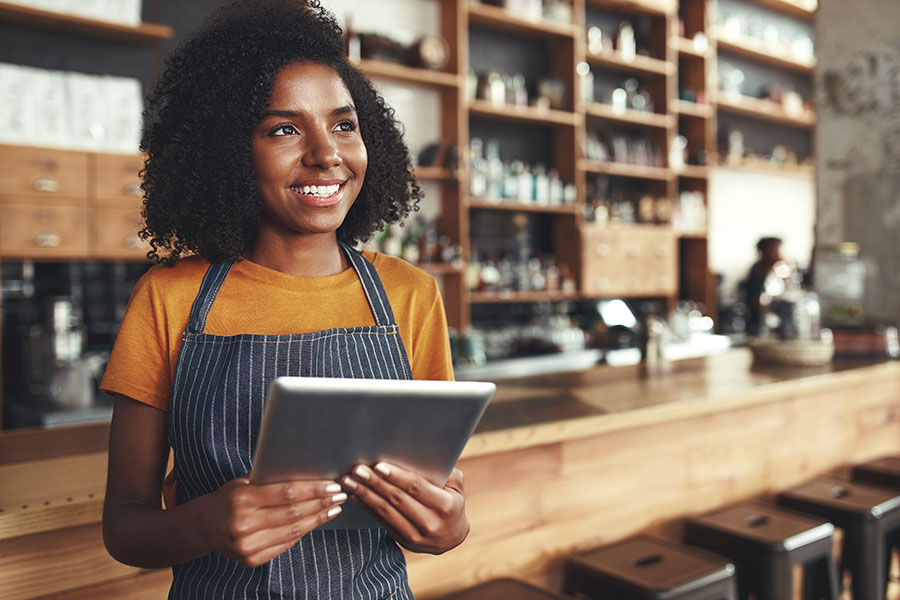 Business Insurance - Smiling Young Business Owner Standing In Her Store While Holding Tablet