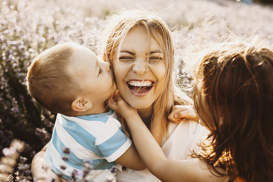 Contact - Laughing Mother And Her Children Playing Outside